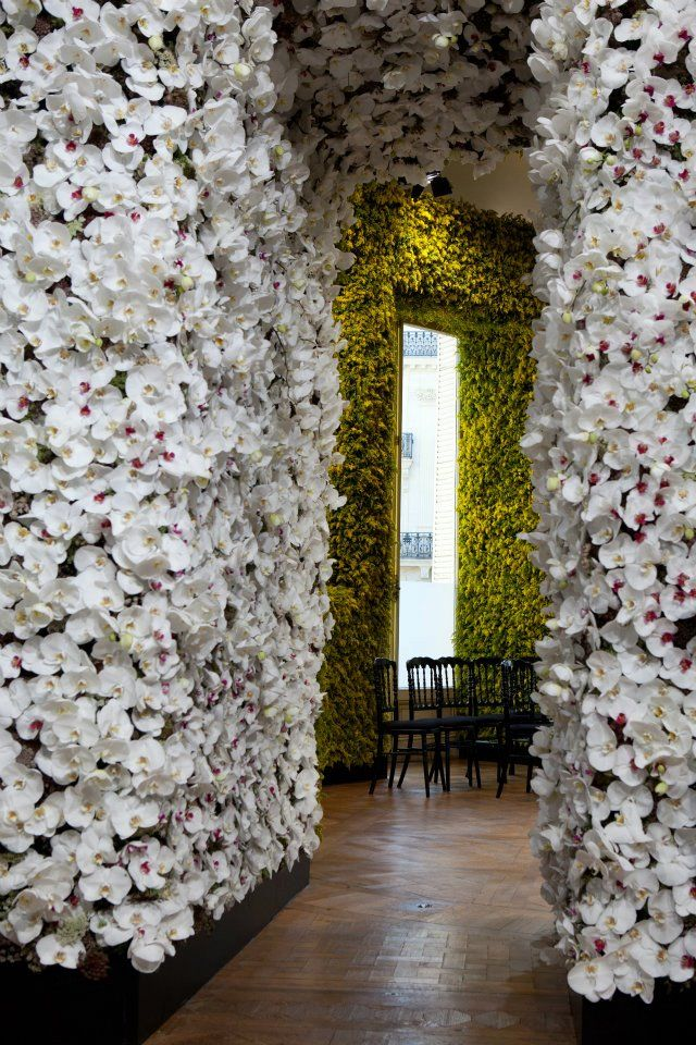 Diors Show-Stopping Set of a Million Flowers. Belgian designer, Creative director, Raf Simons, decorated the Christian Dior Autumn/Winter 2012 Couture Show with one million flowers which were spread out into 5 separate rooms. Each room focused on a particular color, which added to the dramatic effect. The team that put this together used blue delphiniums, white orchids, pink peonies and lots of colored roses.