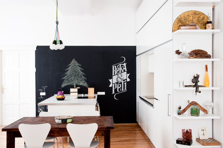 kitchen and living room blend together by placing colorful knick-knacks on the kitchen shelves. chalkboard wall provides for playfulness