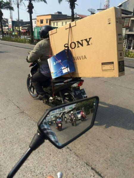 Sony PS4 and Sony 50 inch TV strapped to the back of a motorcycle. Sony should buy this guy a car.