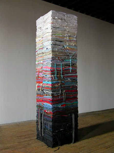 Compression by Derick Melander. Second-hand clothing, wood and steel. 800 lbs. of carefully folded, second hand clothing, crisscrossed around a central spine.