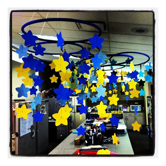 Star mobiles made from construction paper stars cut out with a die cut machine and hula hoops wrapped with blue duct tape. #crafts #stars #inexpensive #yellow #blue