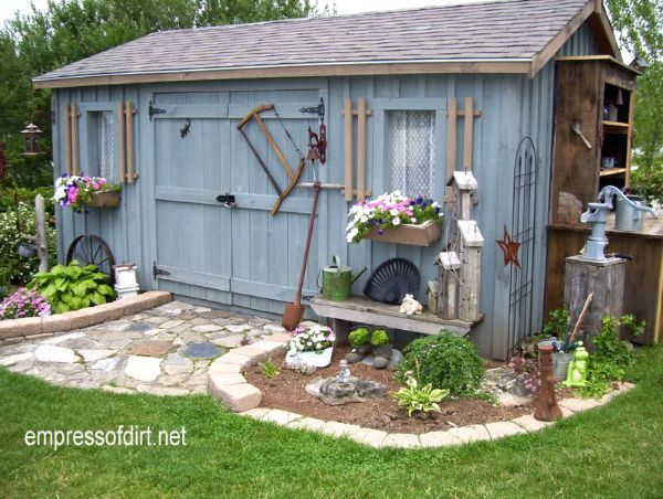Blue barn board shed decorated with old tools and DIY garden art