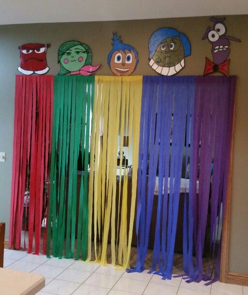 """Inside Out"" themed wall  can be used as picture taking background/photo booth.  Throw some colored balloons in the air and snap a shot of guests with birthday person. You can also add pictures to the streamers(i.e. crying baby pictures on the blue or red streamers, laughing and smiling pictures on the yellow streamers, etc.) Or you can create the memory bank off to the side of your wall by cutting out circular shaped construction paper and placing the coordinating pictures with the colored…"