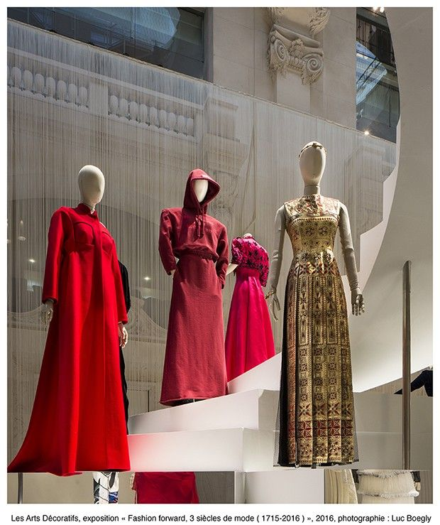 A installation of contemporary clothing featuring a hooded red jersey sweatshirt and skirt by Vetements, centre (Foto: Les Arts Décoratifs)