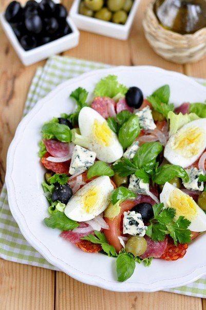 Каталонский салат  Ингредиенты:      Салатные листья     Лук белый — 13 шт.     Помидор — 1 шт.     Яйцо куриное вареное     Оливки и маслины — 10 шт.     Колбасы сыровяленые (несколько видов) — 100 г (можно добавить хамон или салями)     Несколько веточек петрушки или базилика     Масло оливковое — 1-2 ст.л.     Сыр с голубой плесенью — 30 г