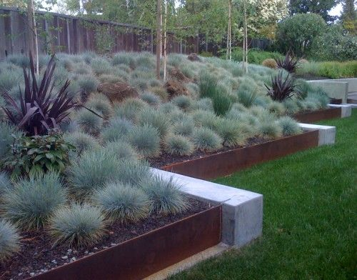 Retaining Walls: Sometimes just a little bit of texture is all it takes. Rust-ridden sheet metal not only contains your planting beds, but its appearance will actually change over time. The patina will continue to change the longer it's exposed to the elements.(Per Houzz)