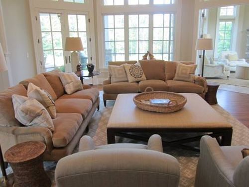 """Mrs. Howard: One of our favorite configurations for a family room is two sofas and two chairs arranged in a U shape around a large square ottoman. I call this """"stadium seating."""" I think it is important to be able to spread out and be relaxed in a family room, so comfort is our first objective - always."""