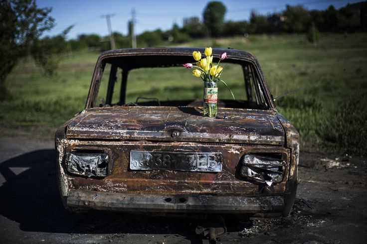 """From National Geographic: """"A bouquet of flowers is placed atop the burnt out shell of a car where clashes between pro-Russian gunmen and the Ukrainian army took place, four kilometers (2.5 miles) north of Slovyansk, Ukraine, on May 7, 2014. (AP Photo/Manu Brabo)"""""""