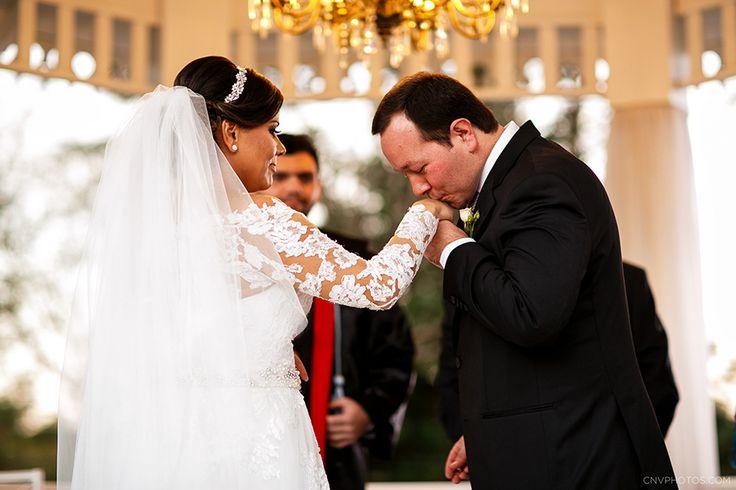 Noivo beijando a mão da noiva no altar