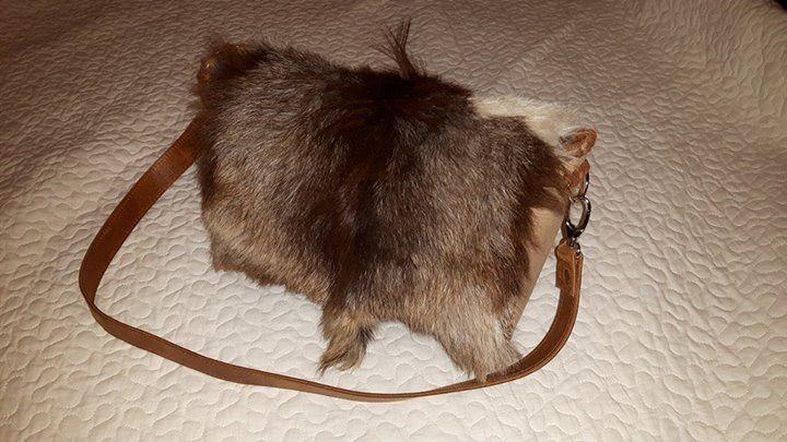 Schoudertas in bruintinten met lederen zijkanten en schouderband. De bovenkant is een geitenvacht.