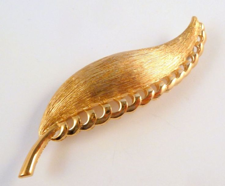 Vintage large textured and polished gold tone, curved leaf brooch by designer Monet. Circa 1970's.