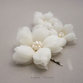 "The floral wedding headpiece consists of three wedding hair flowers. The flower wedding headpiece is handcrafted with high quality materials and attention to detail craftsmanship. . This petals are hand cut and hand pressed. Flowers petals are made of 100% silk and adorned with large clusters of freshwater pearl and Swarovski crystals. The large bridal hair flower measures approx. 3 in diameter. The two small wedding hair flowers measure approx. 2""-2.25 in diameter. Color choices of the…"