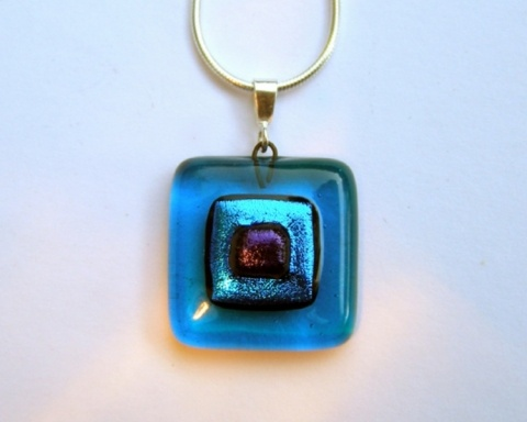 "Paula Woodward - A square fused glass pendant with layers of turquoise and blue glass. The base is a deep transparent turquoise with layers of iridescent aqua and blue dichroic glass.   The pendant is fitted with a sterling silver bail and comes complete with a 16"" or 18"" sterling silver snake chain. £22"