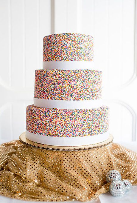 Sprinkle Wedding Cake with White Fondant and Rainbow Nonpareils . Ribbons of white fondant break up the sprinkle-covered tiers of this big day dessert.