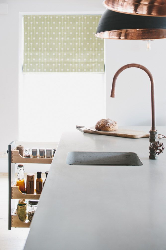 Polished concrete island worktop with bespoke copper tap works well with hanging pendant lights from Original BTC. A tiered spice oak drawer is visible.