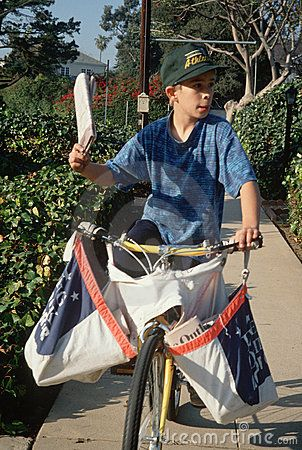 Newspaper delivery boy on bicycle, Los Angeles, California