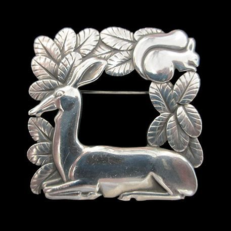 Georg Jensen Deer and Squirrel Silver Brooch by Arno Malinowski |   A typical Art Deco early design from Arno Malinowski for Georg Jensen of a silver brooch depicting a seated deer in profile resting amongst foliage with a squirrel above in the leaves. Circa 1930s.
