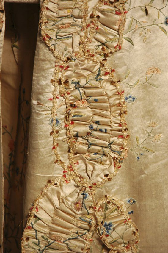 """Open-front sack-back gown, 1760s. The fabric was made and embroidered in China specifically for export to Western markets. The design is a meandering floral with ruching and chenille trim. In addition to the indicative Chinese embroidery, the fabric of this gown is 29 ¼"""" wide with tempole holes in the yellow selvages, clear indications of Chinese manufacture."""