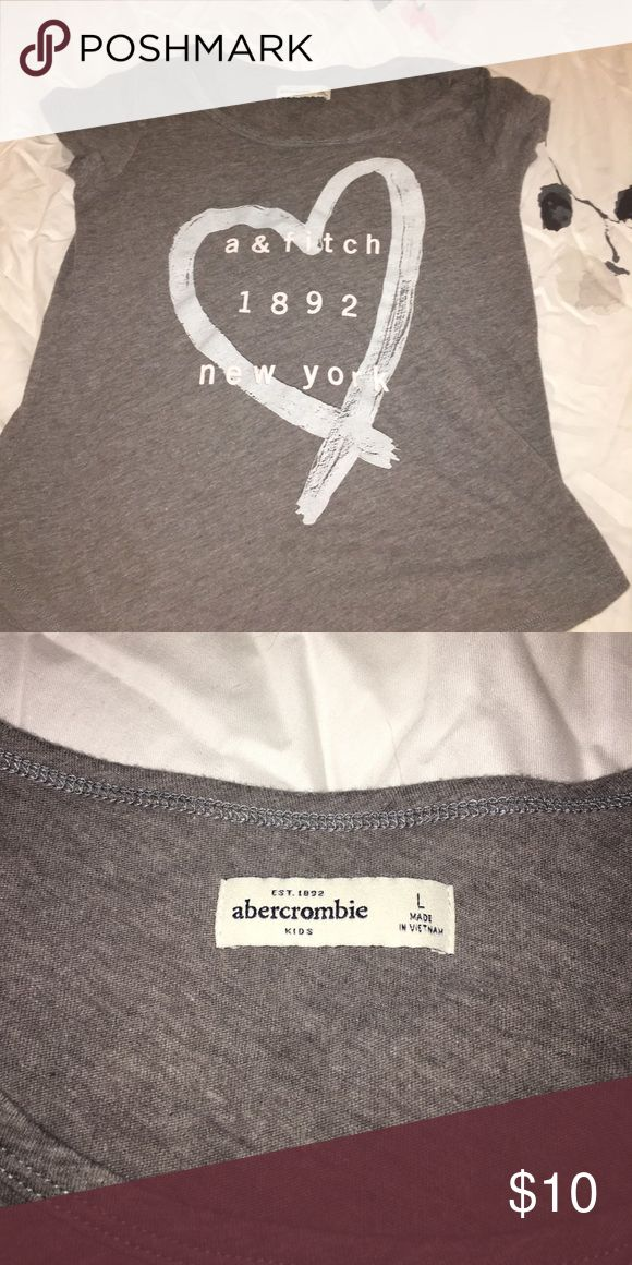abercombie kids Gray T-Shirt This is an abercombie kids gray t shirt with a blue heart on it and pink writing. It is an L in a kids size. but it fits me and I'm an xs and s in adult sizes. This is super cute and I'm perfect condition, I'm open to any offers! abercrombie kids Shirts & Tops Tees - Short Sleeve