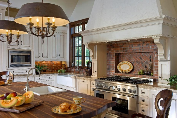 English Cottage style kitchen with brick backsplash. I love the way the range is with that big extended hood.