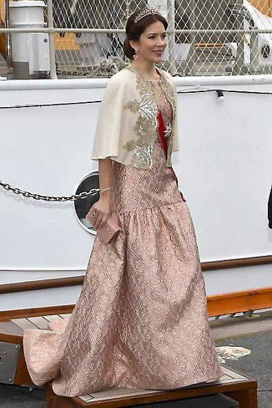 Crown Princess Mary of Denmark accentuated her figure in a floor length patterned pink dress with nipped in waist. She kept her dark tresses in a simple up do but finished off her look with a dazzling tiara and sparkling pink clutch bag.