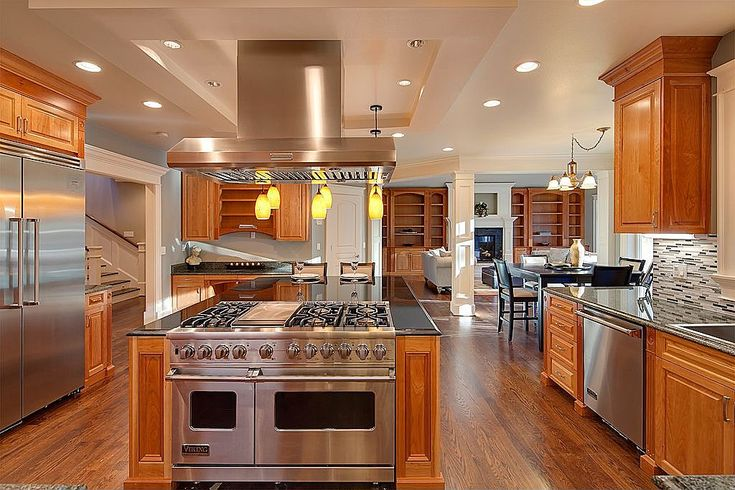 A spacious, luxurious kitchen with a center range on the island and beautiful warm oak cabinets. Do you like the red-orange oak? Source: https://www.zillow.com/digs/Home-Stratosphere-boards/Luxury-Kitchens/
