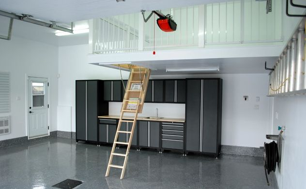 High ceilings can make up for limited floor space in smaller garages. This loft  acts like an attic, with a low-clearance ceiling height and retractable ladder. The railing ventilates the space and cut down on building costs. #Loft #GarageLoft #Garagestorage