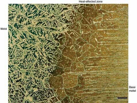 Microstructure of 7-Mo PLUS duplex stainless steel (Fe-_0.03%C-_2%Mn-27.5%Cr-4.85%Ni-1.75%Mo-  0.25%N) welded with Nitronic 50, etched with Beraha's BI reagent, and viewed with bright-field illumination.  Ferrite is colored, and austenite is unaffected. The magnification bar is 200 lm long.