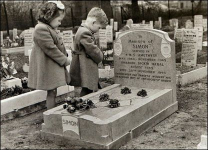 Two children stand at the grave of Simon. Simon the cat is credited with helping save the lives of Royal Navy officers during the Chinese civil war in 1949. He protected food stores from a rat infestation during a siege.