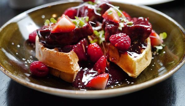 Belgian waffles with crispy pork belly and berry compote at Tanta Restaurant in Chicago.