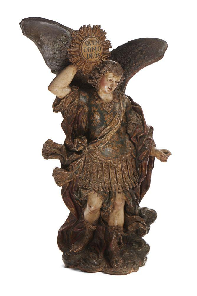 """São Miguel Arcanjo, escultura em barro policromado, de final do séc. XIX. São Miguel está representado de pé assente sobre nuvens, traja vestes romanas e calça sandálias, com manto em tons de encarnado e dourado e espada à cintura. A mão direita levantada segura uma placa com resplendor, com inscrição """"QUEM COMO DEOS""""."""
