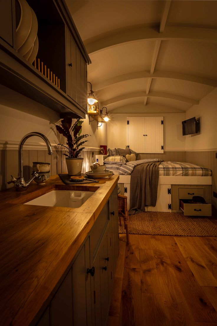 Interior of a Poachers Hut by The English Shepherds Hut Company. It features a built in kitchen, ensuite bathroom, wood burning stove and a double bed.
