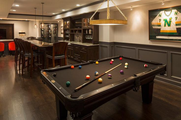 Basement boasts a built in wet bar next to a black pool table placed in front of a wall fitted with charcoal gray wainscot trim.