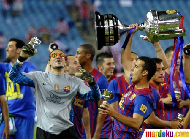 Pemain Barcelona, Pedro Rodriguez (kanan) mengangkat piala bersama rekan satu timnya setelah memenangkan pertandingan final Piala Raja Spanyol melawan Athletic Bilbao di Stadion Vicente Calderon di Madrid.