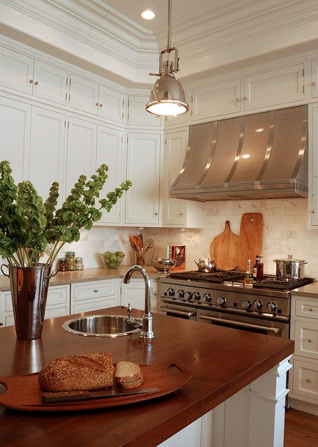 Stainless Range Hoods - Design Chic- love the warmth of wood on the island and the flower arrangement…
