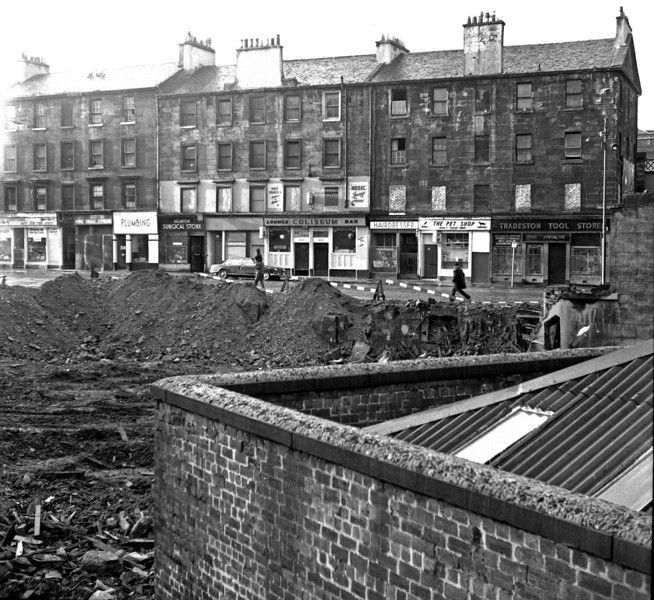 Eglinton St, west side between Cook St and Wallace St, after some recent demolition. The Coliseum Bar was notable for a collection of photographs on display, showing stars of music-hall and cinema who had popped in for a quick one after a show or a premiere at the Coliseum across the road. I suppose the roof in the foreground must have belonged to the old Bridge St subway station. December 1973