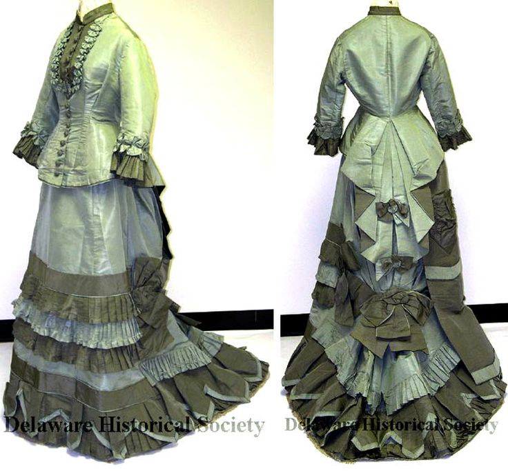Two-piece dress, Mme. Lamy, Paris, ca. 1875-76. Pale green ribbed silk w/gray-green silk trim. Front-fastening peplum bodice, boned; 16 pale green silk-covered buttons & gray-green placket trimmed w/rosettes. Long sleeves trimmed w/pleated ruffle & band of pale green rosettes encircling wrist. High band collar trimmed inside w/hand-made bobbin lace. Pleated panel in back w/2 gray-green bows. Ruffled, pleated skirt w/bobbin lace trim, lined in white polished cotton. Delaware Historical…