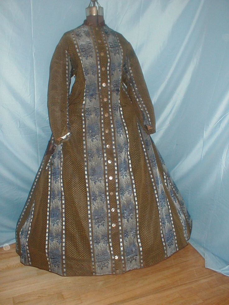 "Antique 1860 Wrapper Dress Bown and Royal Blue Stripe Silk; fully lined in cotton, piping at neck & armscyes, front button closure, two side pockets trimmed in brown satin, minor underarm discoloration, bust: 36: length: 52-58""; hem width: 140""."
