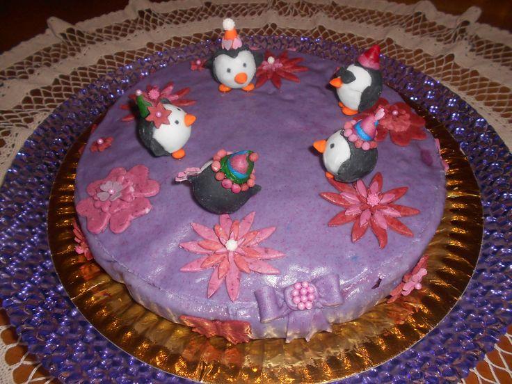 Torta con cioccolatini sferici trasformati in pinguini su sfondo floreale viola.