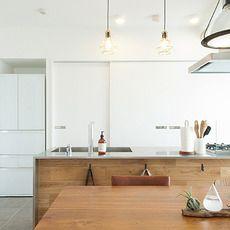 引き戸収納でスッキリとした背面はホワイトカラーでまとめて、キッチン、ダイニングテーブル等はナチュラルカラーの木材を使ってメリハリを出しています。 とても清潔感を感じる明るいキッチンスペースですね。