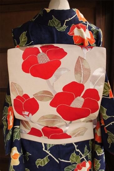 ベージュグレーに近い生成り色の地に、深みのある赤が美しく映える夢二好みの椿模様が織り出された袋帯です。