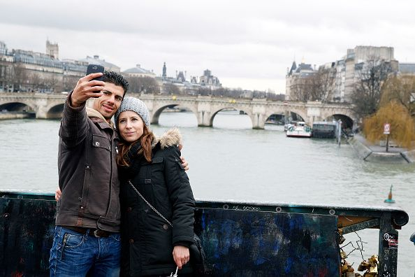 A couple take a selfie on the Pont des Arts during Valentine's Day on February 14 2014 in Paris France Officials from Paris City Hall have placed...