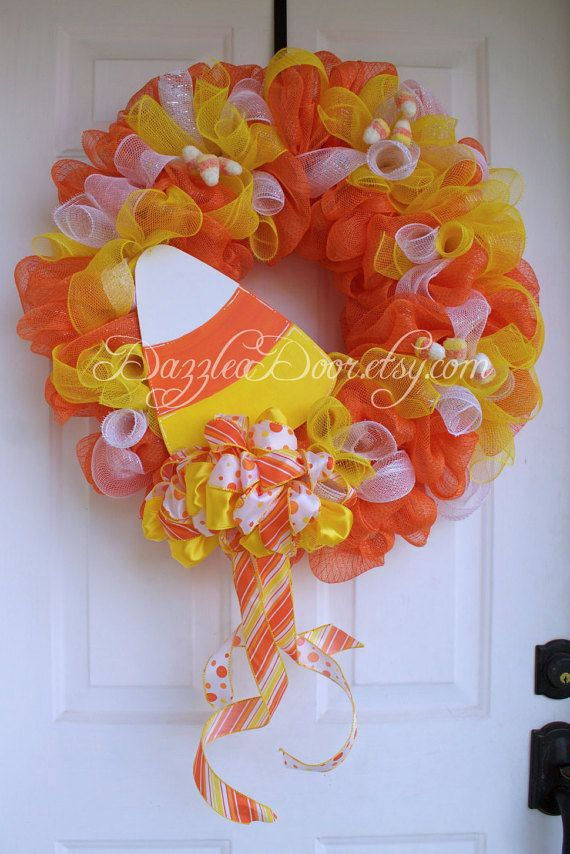 Its all about the candy at Halloween and this Candy Corn inspired wreath is bright and full of color to highlight your door and welcome all who visit or come to taste of your treats. Orange deco mesh creates a base for this candy influenced wreath and is then highlighted with white and yellow deco mesh. Glittery candy corns are clustered together and attached with color matched pipe cleaners to add extra dimension to this beautiful wreath. The final touch is a hand painted wood candy corn…