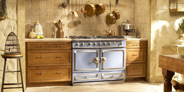 blue stove, wood cabinets, and tile