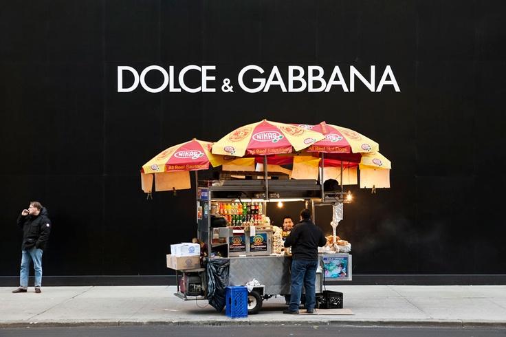 "By Natan Dvir ""Dolce Gabbana #01,"" 2012. A hotdog vendor talks to a customer next to a future Dolce Gabbana store on 5th Avenue"
