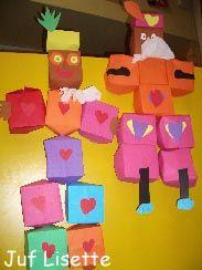 """* Carlos is verliefd! Benodigdheden: Vouwblaadjes, gekleurd papier, wit crêpepapier of """"taartkleedjes"""", lijm,schaar, nietmachine. Vouw eerst 16 vierkantjes, knip in en maak hier doosjes van. Er zijn 9 doosjes nodig voor deze Piet. De Piet krijgt een kraag en wordt in elkaar geniet."""