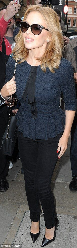 Perfect in a peplum: Kylie looked polished in a navy pussy bow top and black skinny jeans for the album launch