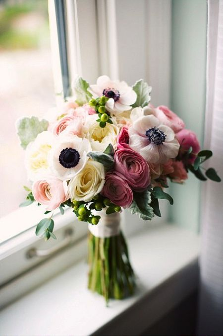 Beautiful bouquet of ranunculus, anemones, garden roses and hypericum.