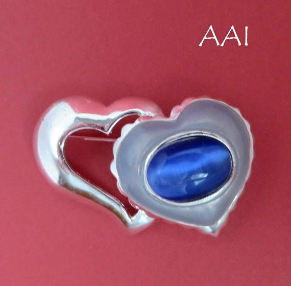 AAI Blue Heart Brooch.  Heres a Vintage Double Heart Blue Cats Eye Brooch Pin. One heart is open and the other has an oval blue cats eye stone and light blue enamel.  ● The Brooch measures 2 wide x 1-1/4 high ● The blue cat eye stone is 7/8 x 1/2 ● Signed AAI ● It is in good vintage #blueheart #vintagebrooch