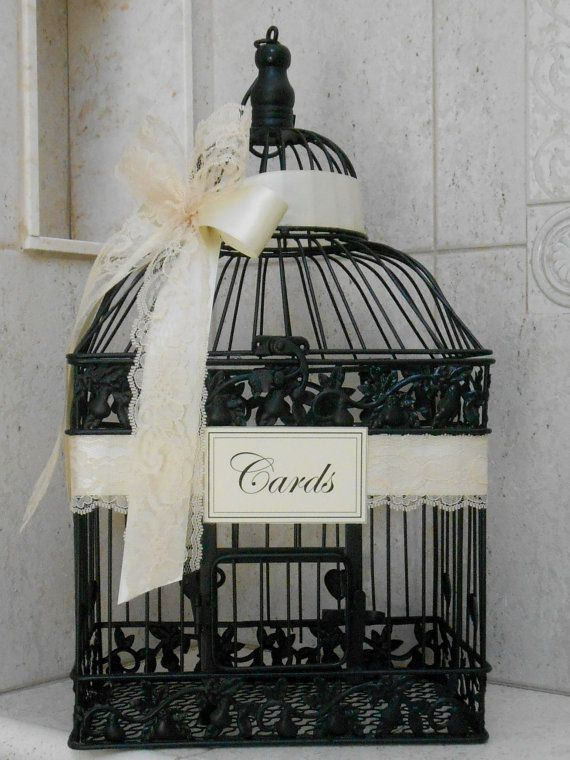 This rustic birdcage has been painted black and is elegantly decorated with satin ivory ribbon, accented with ivory lace, and adorned with a small